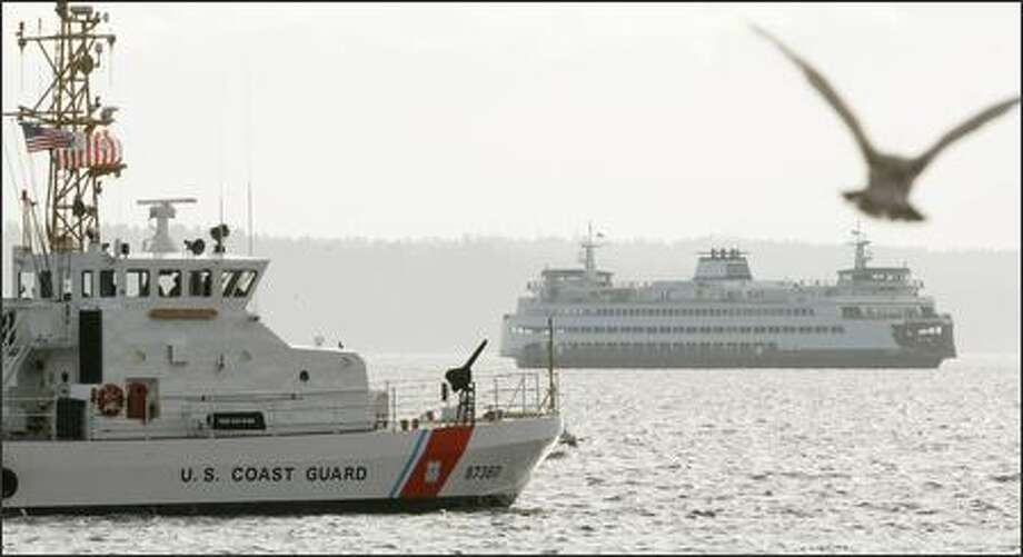 A Washington State ferry and a Coast Guard ship pass in Elliott Bay Wednesday after a man with fireworks in his car caused delays and an investigation at Colman Dock. Photo: Dan DeLong, Seattle Post-Intelligencer / Seattle Post-Intelligencer
