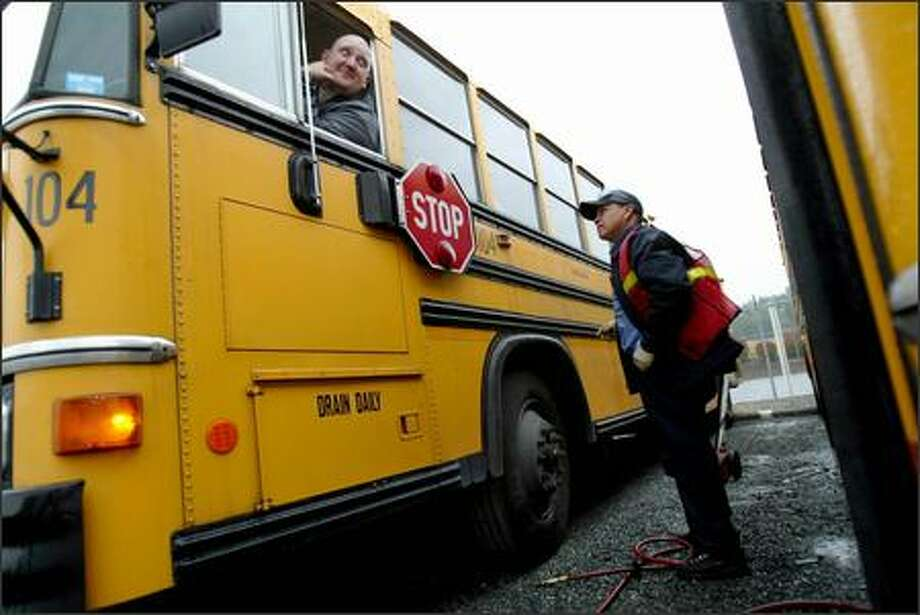 Bus driver Greg Thomas of the Renton School District gets ready to leave the bus barn after Agustin Serano refilled the tires on his bus.  Vandals let the out of the front tires on every one of the district's school buses overnight, delaying classes by two hours district-wide -- and closing Renton -- on the last day of the school year. Photo: Karen Ducey, Seattle Post-Intelligencer / Seattle Post-Intelligencer