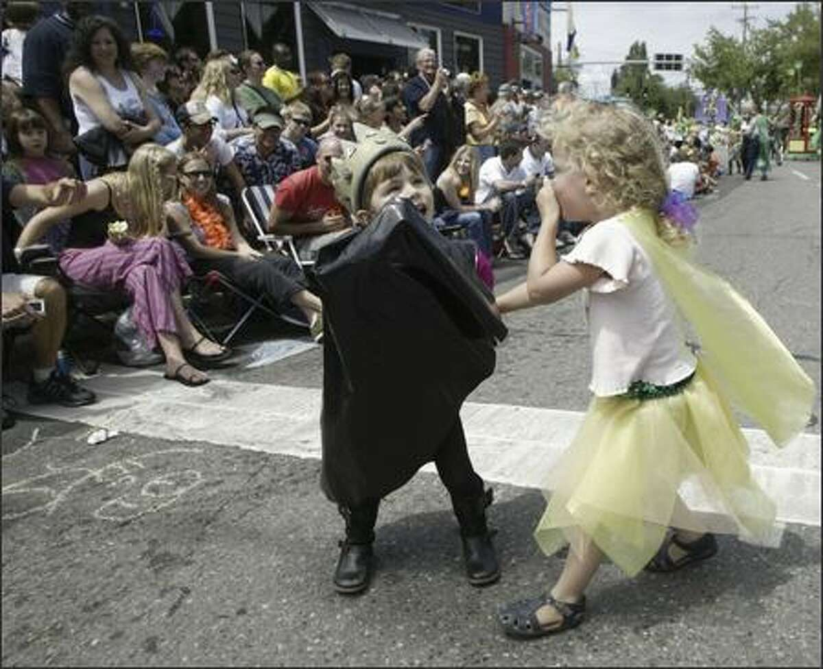 Jasper Toms, right, and Jade Weston hold hands while marching in the 18th annual Summer Solstice Parade in Fremont.