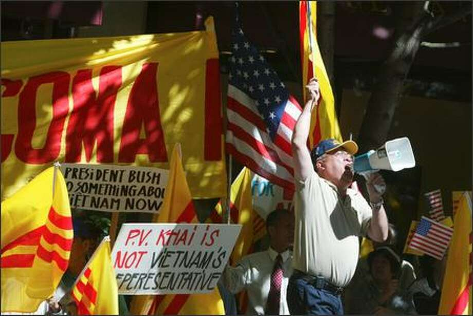 Robert Tran of Tacoma protests yesterday at the Fairmont Olympic Hotel against the Seattle visit of Vietnam's prime minister. He says the Communists killed his brother in 1975. Photo: Karen Ducey, Seattle Post-Intelligencer / Seattle Post-Intelligencer