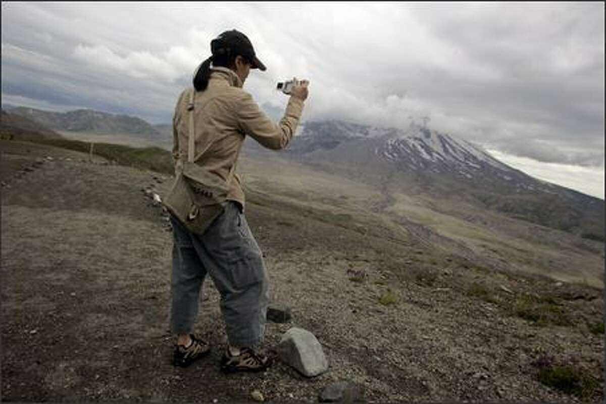 University of Washington systems librarian Anjanette Young photographs Mount St. Helens during a tour of Washington as part of an orientation program to help new faculty learn about the state's geography, history, politics and economy.