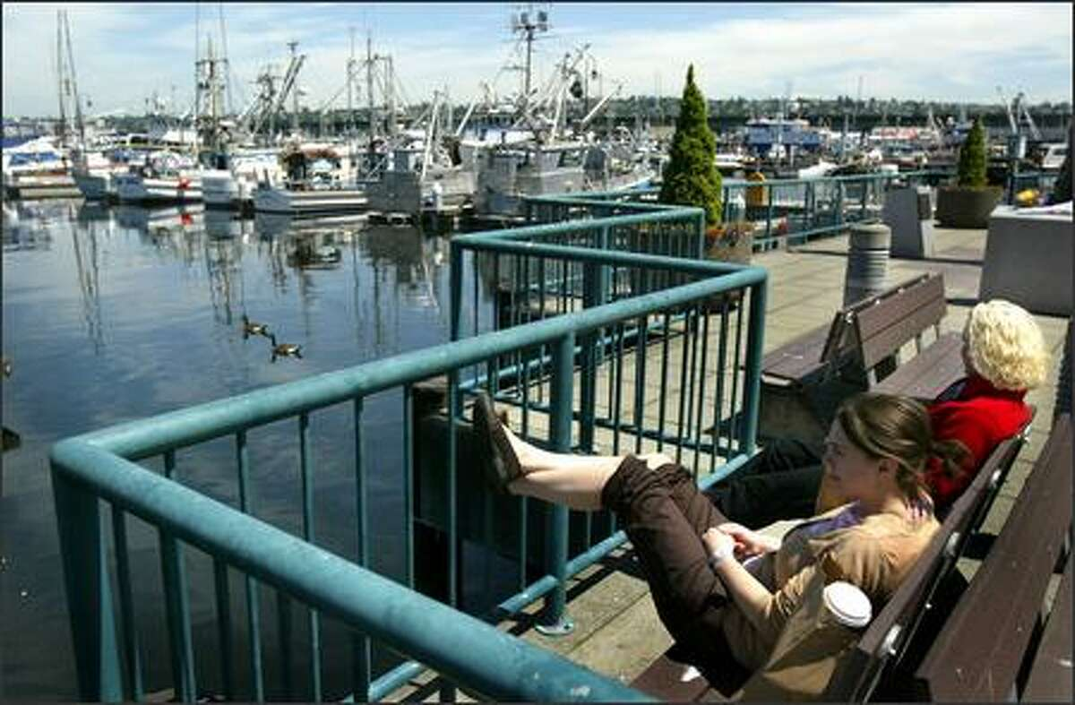 Tracy Buker, foreground, and co-worker Shannon Little take in the scene during their lunch break atFisherman's Terminal in Magnolia.