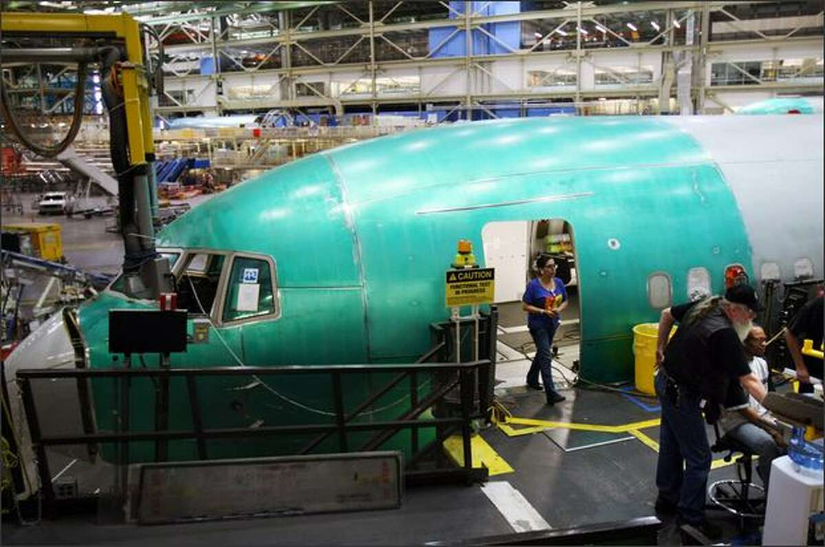 Boeing workers, including electrician Helga Bowlin, from left, and David Hillier and Troy Watson work on the Boeing 767 assembly line.