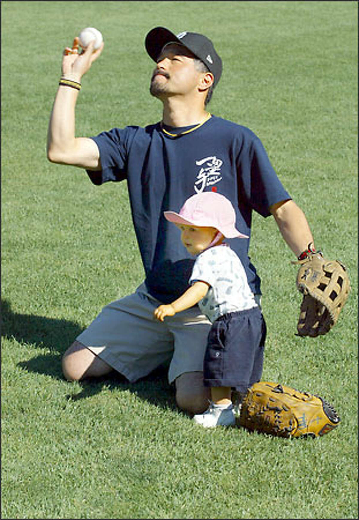 Yoshitaka Inoue tosses a ball to his son yesterday at Safeco Field, while daughter Erina prefers to stay close.