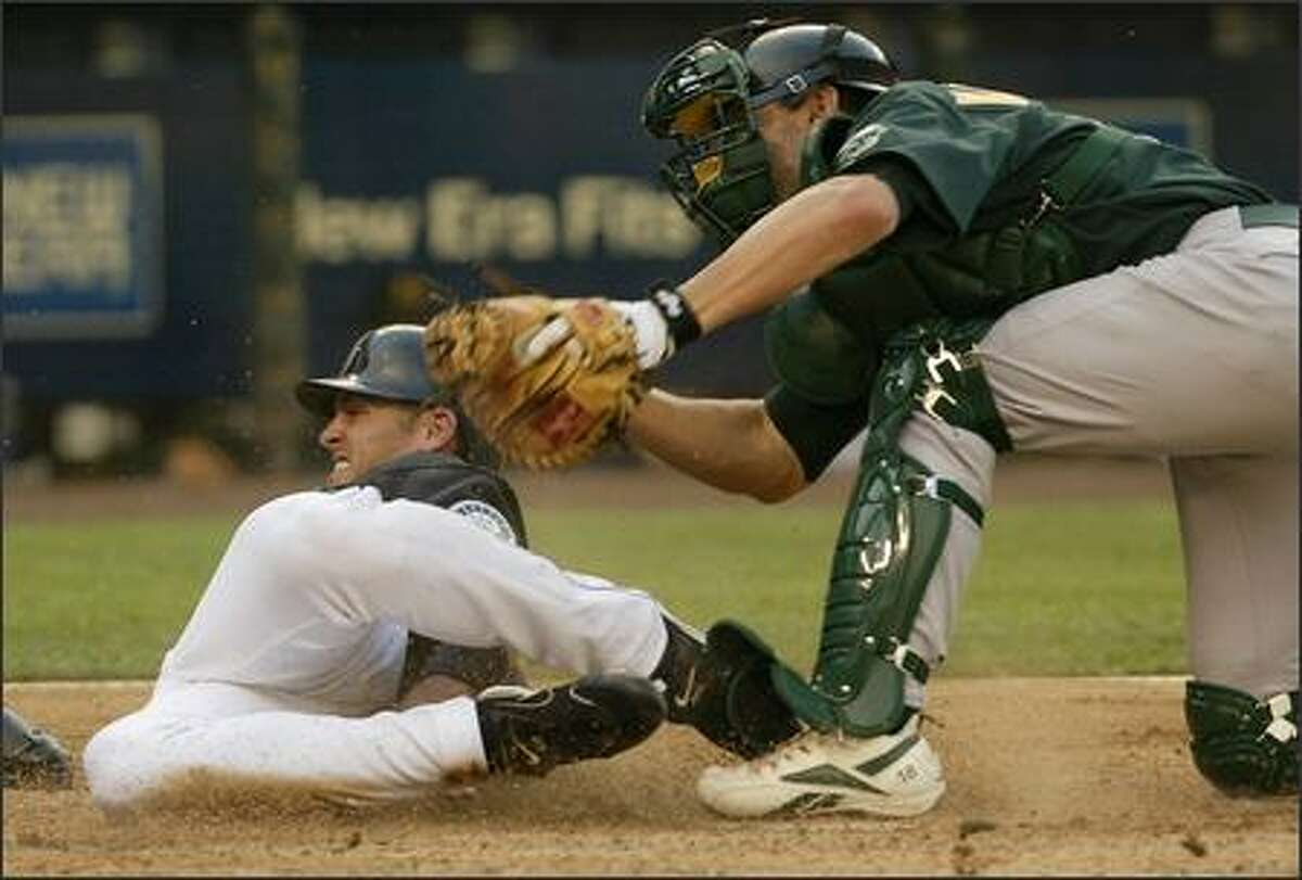 Jeremy Reed slides home safely during the second inning, beating the tag by Oakland catcher Jason Kendall. Reed came home on Ichiro Suzuki's single.