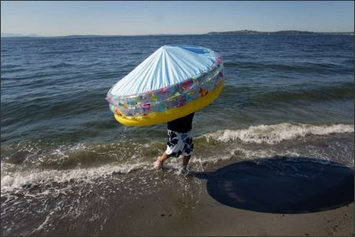 Jose Guerrero of West Seattle leaves the ocean after emptying the pool he took to Alki beach for his kids to play in.