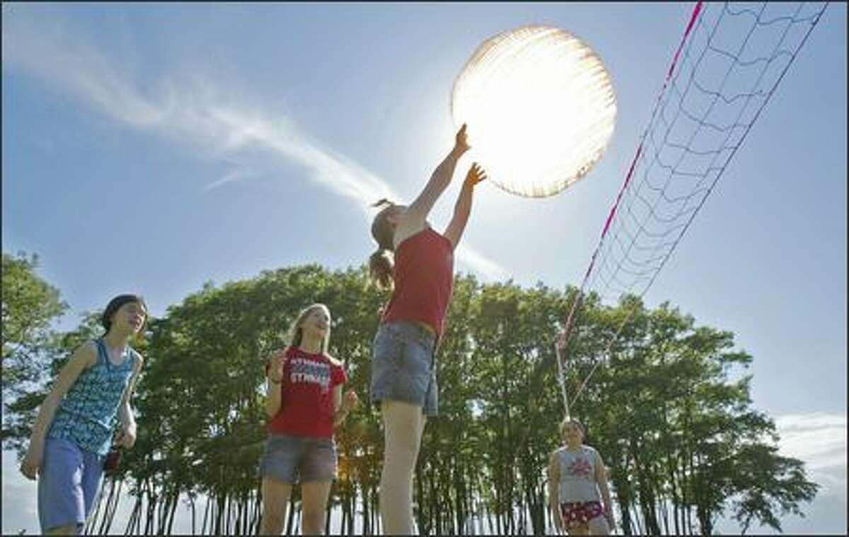 4:20 p.m. -- Elementary students Taki Horiuchi, 10, Claire Overly, 11, Hannah Oliason, 10, and Isabella Fiattarone, 10, seem to be playing with the sun itself as they play volleyball with an oversized plastic ball at Golden Gardens park during a last-day-of-school party Wednesday.