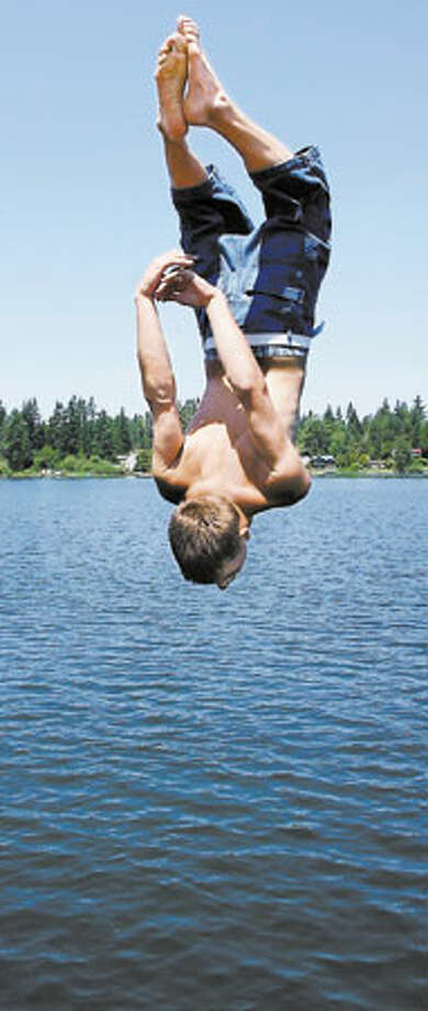 Cliff Swanson, 17, of Marysville does a back flip off the railing of the dock at Martha Lake Park in Mill Creek. Photo: Meryl Schenker, Seattle Post-Intelligencer / Seattle Post-Intelligencer