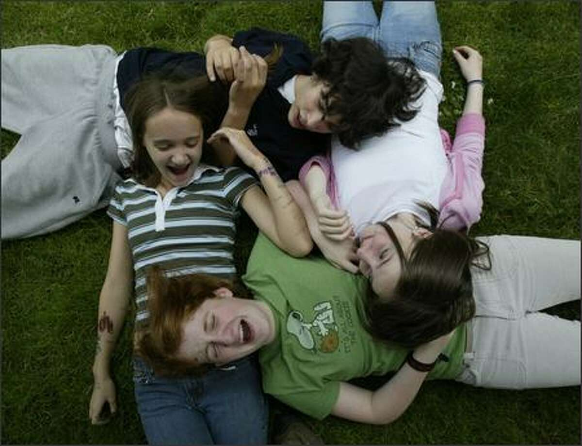 Friends (clockwise, from left) Samantha Wennerlind, Leo Friedman, Kate Collins and Rose McCarty enjoy the start of summer after their last day of 7th grade at Washington Middle School. The foursome was relaxing in the front lawn of Stevens Elementary School in Seattle's Capital Hill neighborhood. They all attended Stevens and had returned to watch the kickball game between faculty and 5th graders.