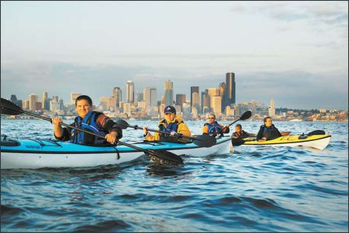 As the evening sun glints off the Seattle skyline, paddlers, from left, Vlad Stets and Ulyana Voronova, visiting from Moscow, Russia, and the Clyde family -- Ian, 6-year-old Marcus and Megan of Bainbridge Island -- take a kayak tour on Elliott Bay.