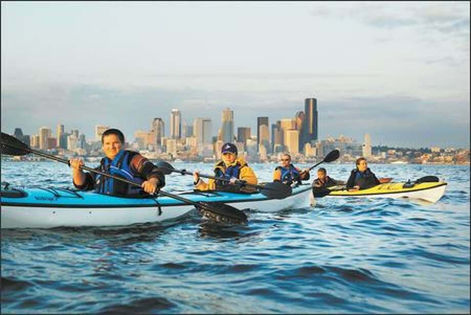 As the evening sun glints off the Seattle skyline, paddlers, from left, Vlad Stets and Ulyana Voronova, visiting from Moscow, Russia, and the Clyde family -- Ian, 6-year-old Marcus and Megan of Bainbridge Island -- take a kayak tour on Elliott Bay. Photo: Dan DeLong, Seattle Post-Intelligencer / Seattle Post-Intelligencer