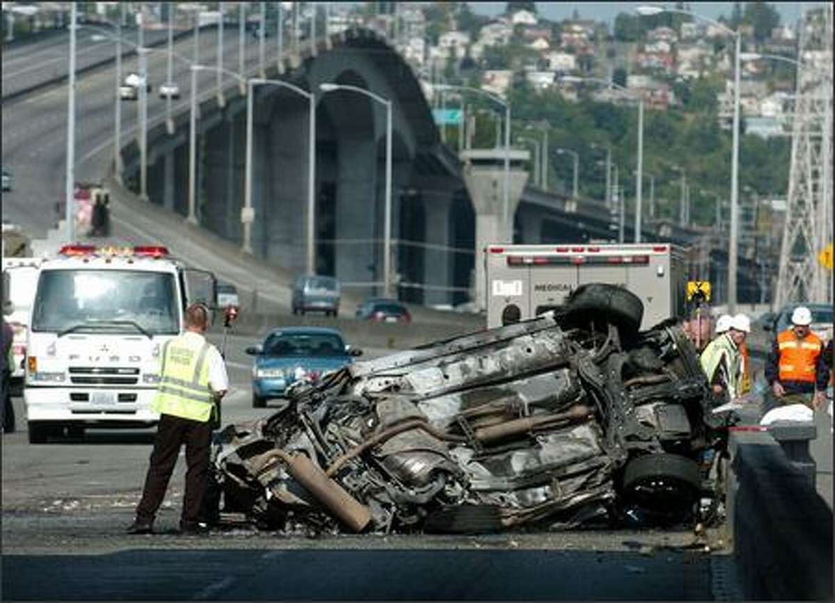 A car traveling eastbound over the West Seattle Bridge early Thursday struck the median at the First Avenue offramp, flipped and burst into flames. Three were killed.