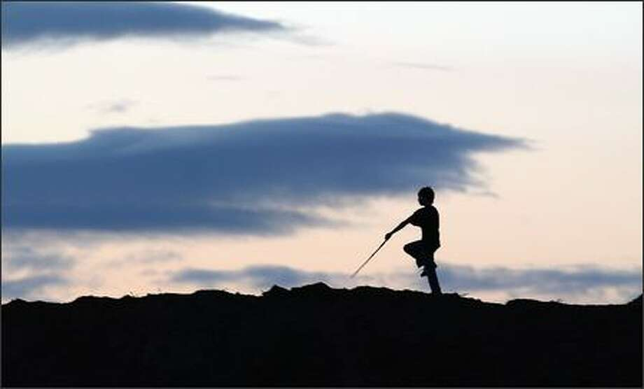 In a scene reminiscent of Peter Pan, a young boy marches across a large mound of dirt as he plays with other boys at sunset in Puyallup. Photo: Gilbert W. Arias, Seattle Post-Intelligencer / Seattle Post-Intelligencer