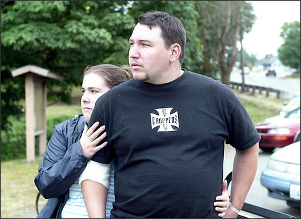 Shaken mill worker Bryce Nichols, 24, is comforted by his wife, Erica, as the couple look over the damage done to the building. Nichols, a maintenance worker, was one of five workers injured in the blast.