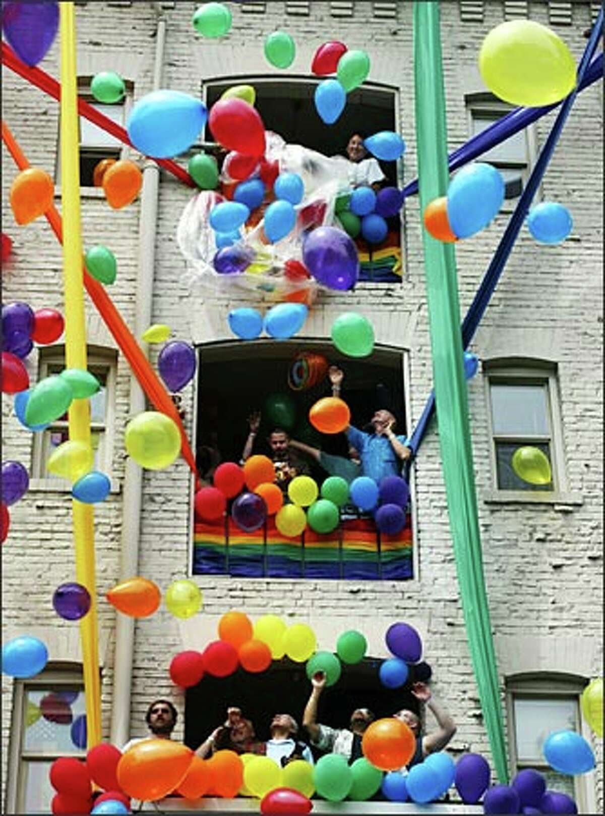 Colorful balloons cascade out of a fourth-floor window on Broadway during the Gay Pride parade on Sunday.