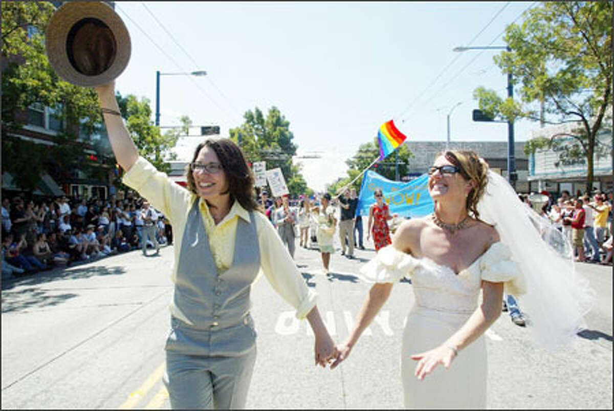 Portraying a just-married couple, Tabitha Warren, left, and Barbara Busetti, both of Seattle, acknowledge the crowd while marching. They are with the organization DontAmend.com, which is trying to stop a same-sex marriage ban amendment.