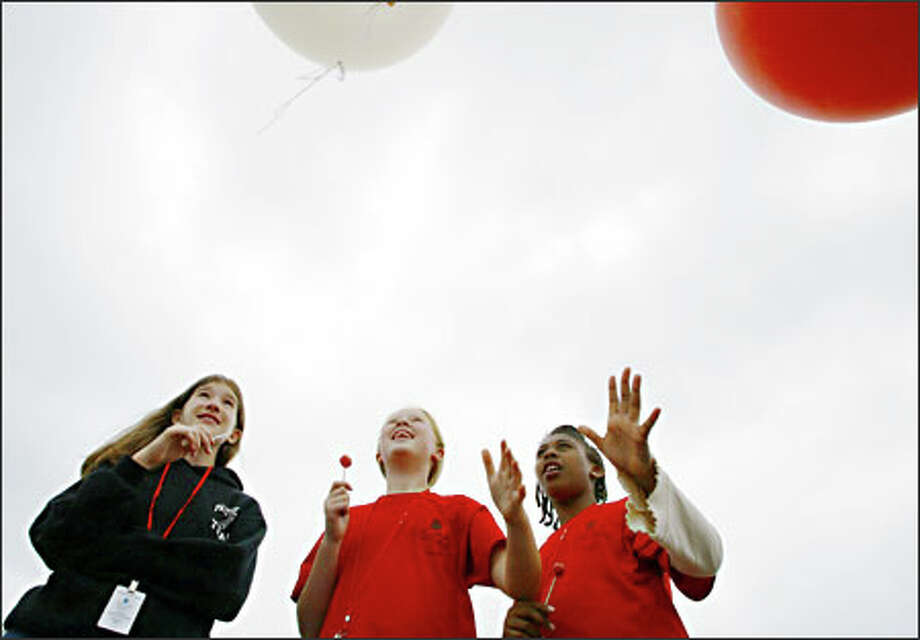 Emily Mathay, center, and Jelani Parker, right, release a weather balloon while Jessica Hale watches. The 12-year-olds were among 65 youths at a weeklong science camp held by the National Oceanic and Atmospheric Administration at its Sand Point complex. The balloons were just one of the sets of experiments. Photo: Meryl Schenker, Seattle Post-Intelligencer / Seattle Post-Intelligencer