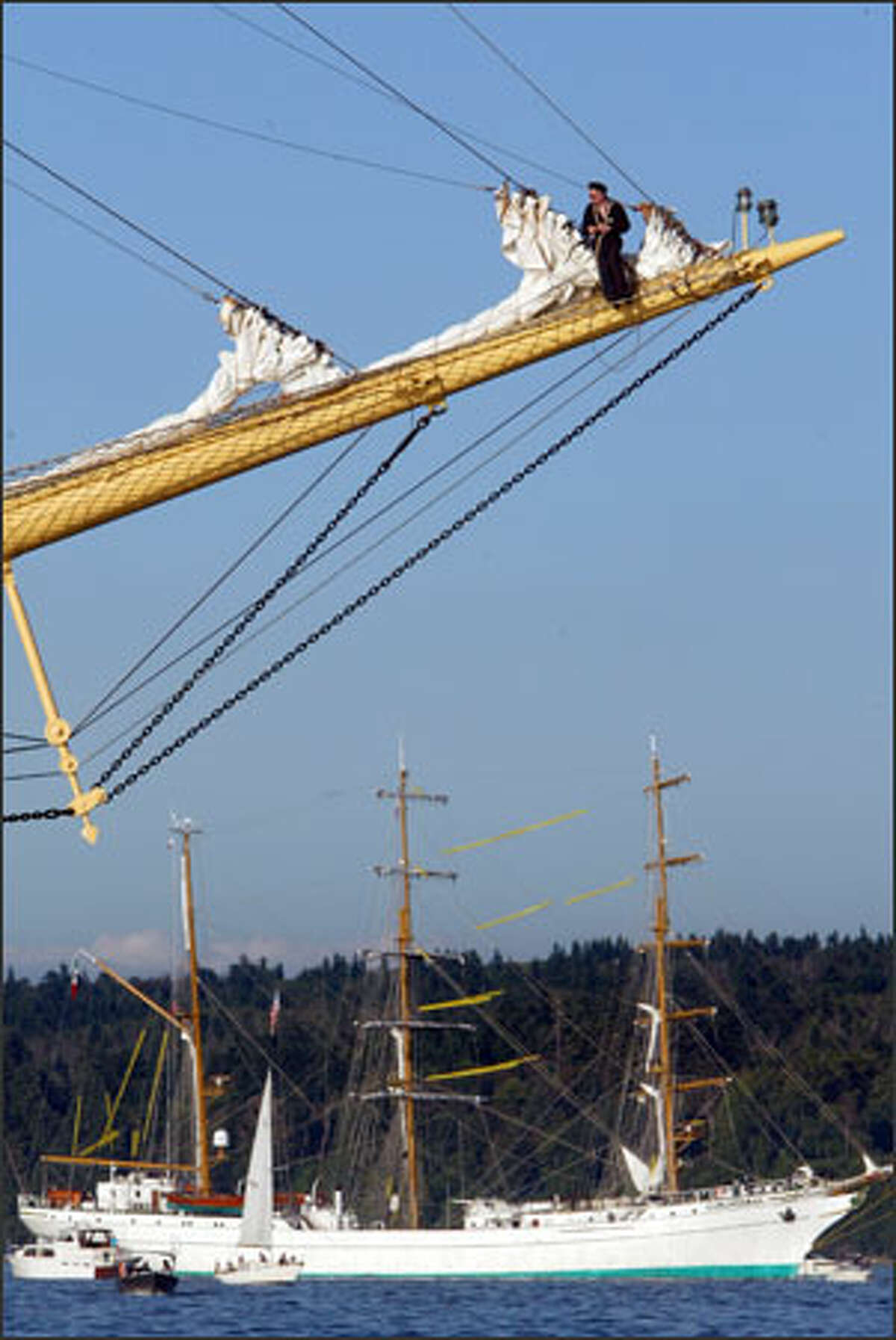 A Russian sailor stands on the bowsprit of the tall ship Pallada with the Mexican ship Cuauhtemoc in the background as the vessels anchor in the waters of Quartermaster Harbor at Vashon Island, in preparation for Tacoma's Tall Ships Festival.