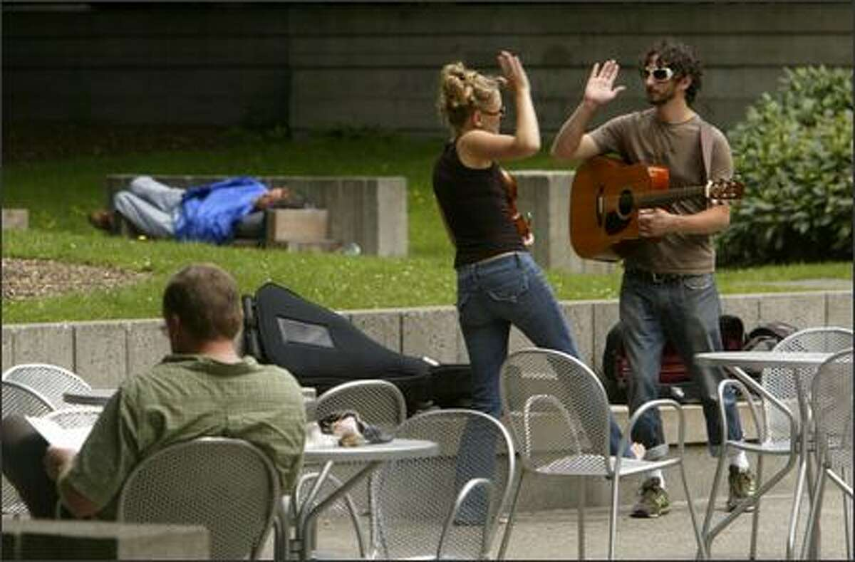 Rachel Jacobson-Larson and Judd Wasserman high-five after finishing a song at Freeway Park. The city is paying buskers $30 to play weekdays at downtown parks.