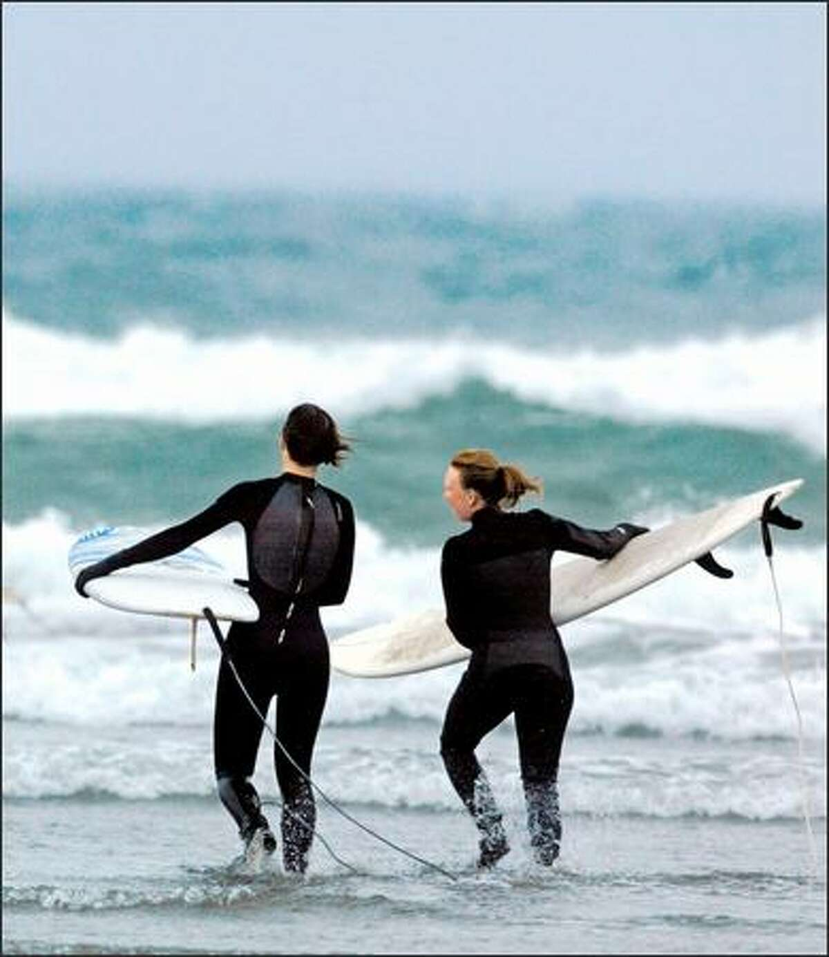 Andrea Platt, left, and Kristi Park, both fromm Seattle, head to the surf at Westhaven State Park in Westport.