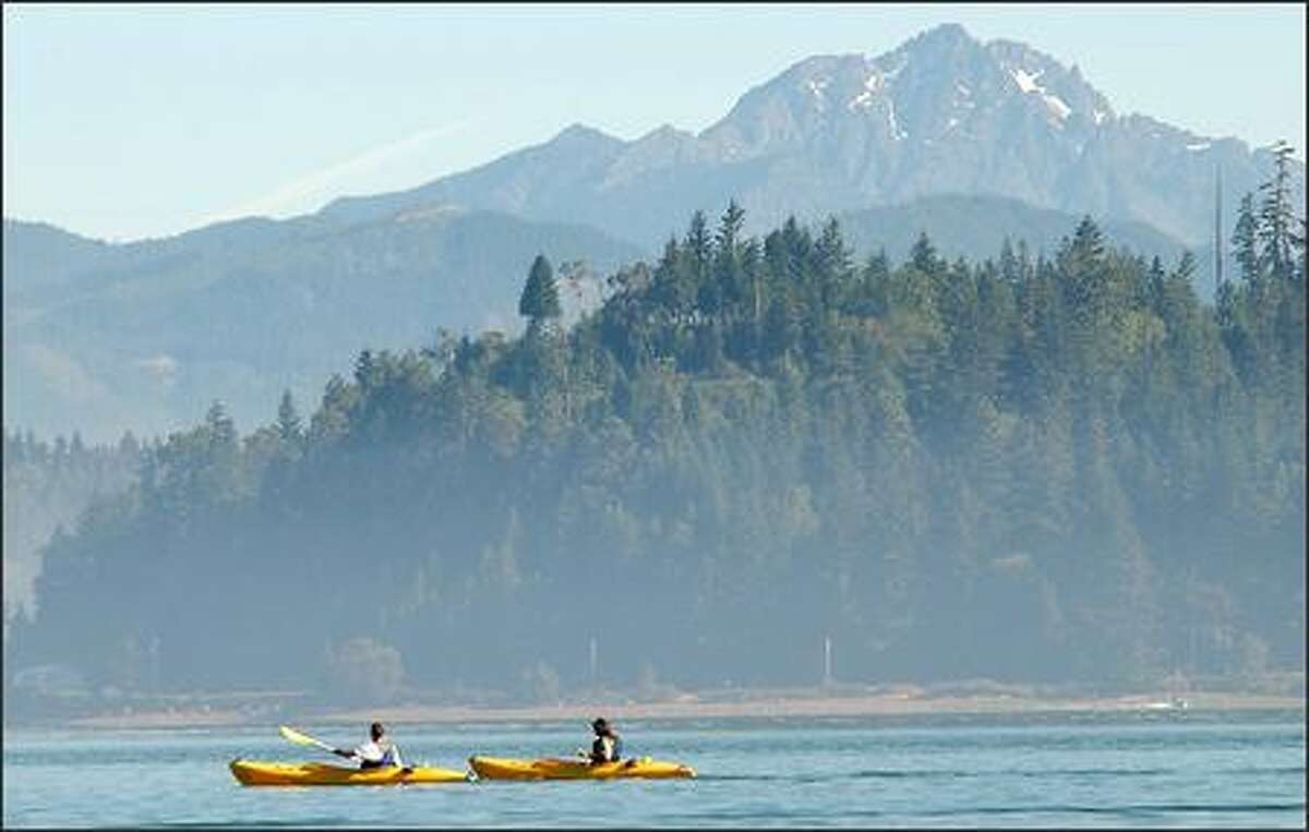 Kayakers cruise the placid waters of Hood Canal near Alderbrook Resort and Spa.