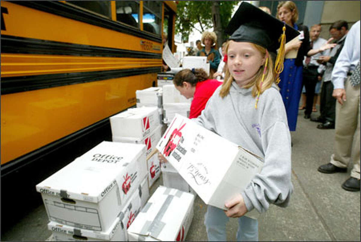 Sporting a graduation cap, 10-year-old Elaine Marshall, a fifth-grader at John Stanford International School, carries a box of petitions for I-884 yesterday in Seattle. The boxes were loaded onto the school bus, which carried them to Olympia. Supporters gathered 327,000 signatures.