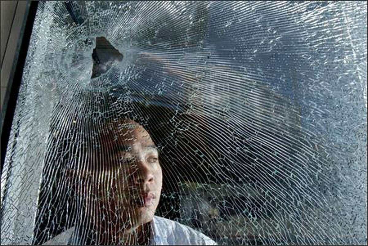 Henry Lo looks out the window of his business in Belltown on Monday. A woman had been shot outside his doorway in the early morning; there was a bullet hole in the front window of his office and blood on the sidewalk in front. Lo also lives on the premises.