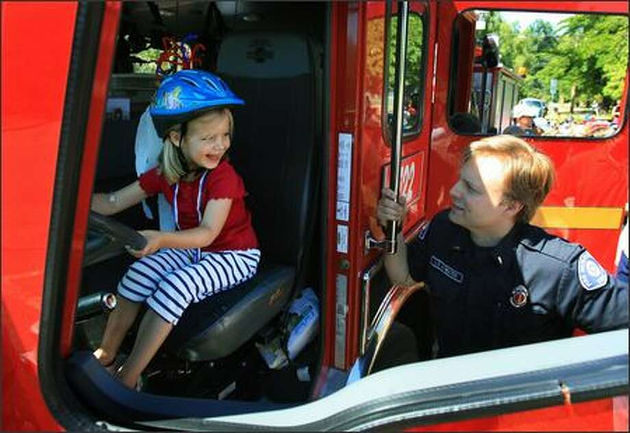 Five-year-old Sasha Balaski smiles at Lt. Paul Atwater while getting her chance to sit in the driver's seat of a Seattle Fire Department truck during the annual Fourth of July parade in Seattle's Montlake neighborhood on Wednesday. Photo: Dan DeLong, Seattle Post-Intelligencer / Seattle Post-Intelligencer