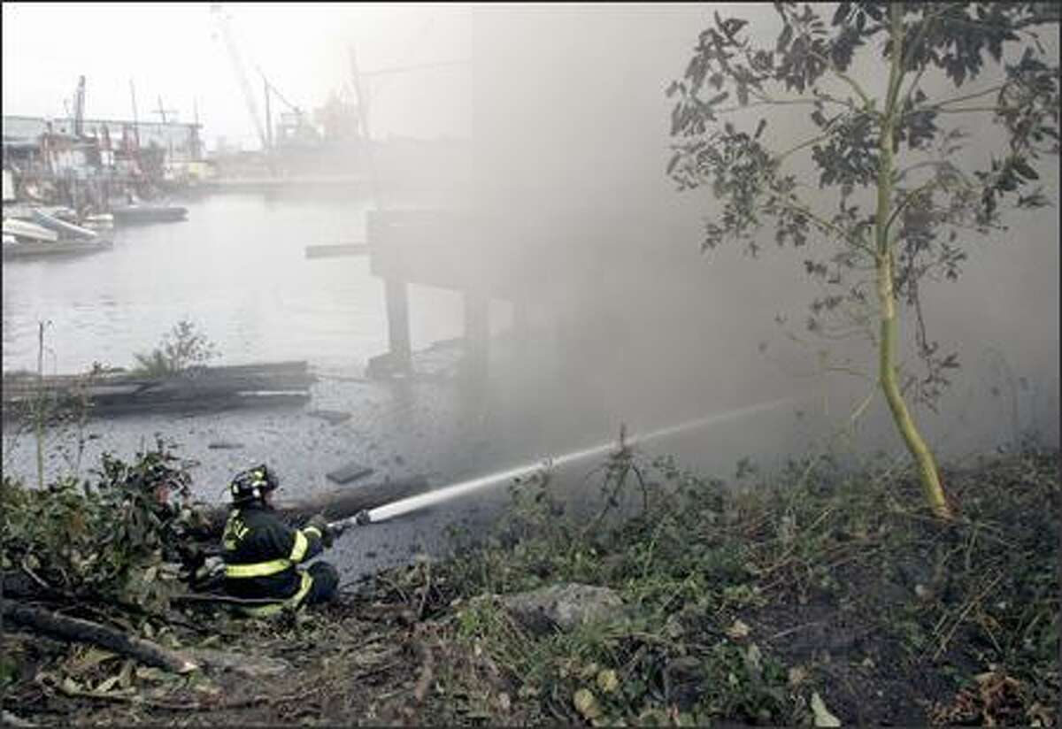 Firefighters work to put out a burning pier on the east side of Lake Union on Wednesday morning. Seattle fire investigators do not yet know the cause of the fire, which was first reported about 1:20 a.m.