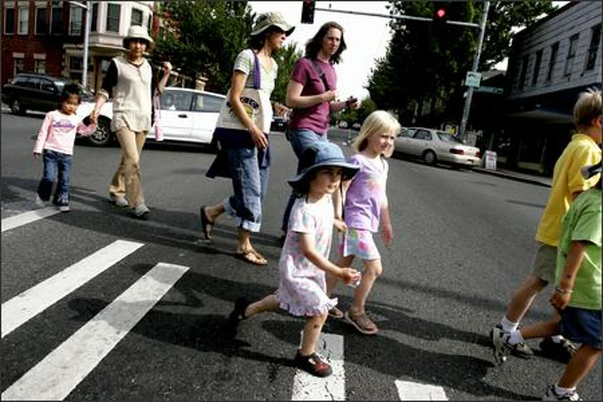 People cross Rainier Avenue S. in Columbia City on their way to the Farmer's Market. Even though Columbia City has experienced a revitalzation, many say that Rainier Valley is an example of neighborhood plans that have been ignored.