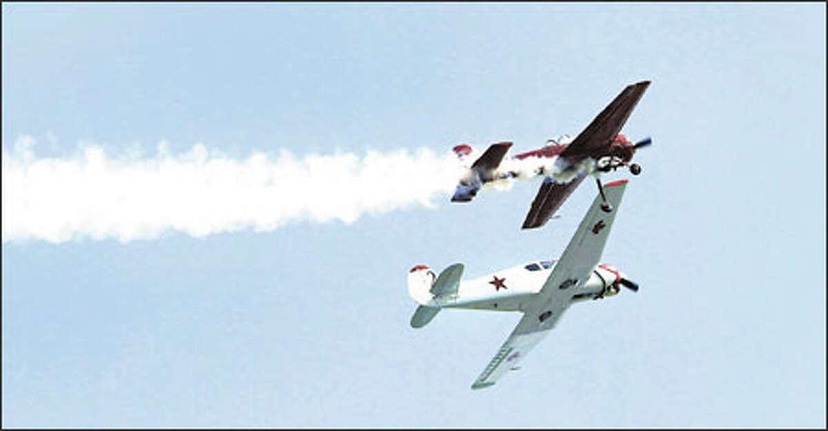 Bud Granley, piloting his Yak 55, flies over his son, Ross Granley, in his Yak 18T during practice runs.