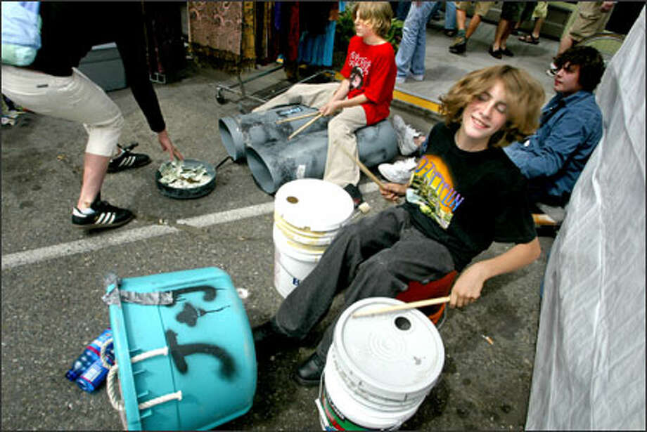 "Who needs expensive instruments? James Squires and Joe Samsel, both 13, are regulars at the Fremont Sunday Market, entertaining passersby with their makeshift drum set. They're called Rain, Squires explained, ""because when we first started, it was pouring down rain on us."" Photo: Karen Ducey, Seattle Post-Intelligencer / Seattle Post-Intelligencer"