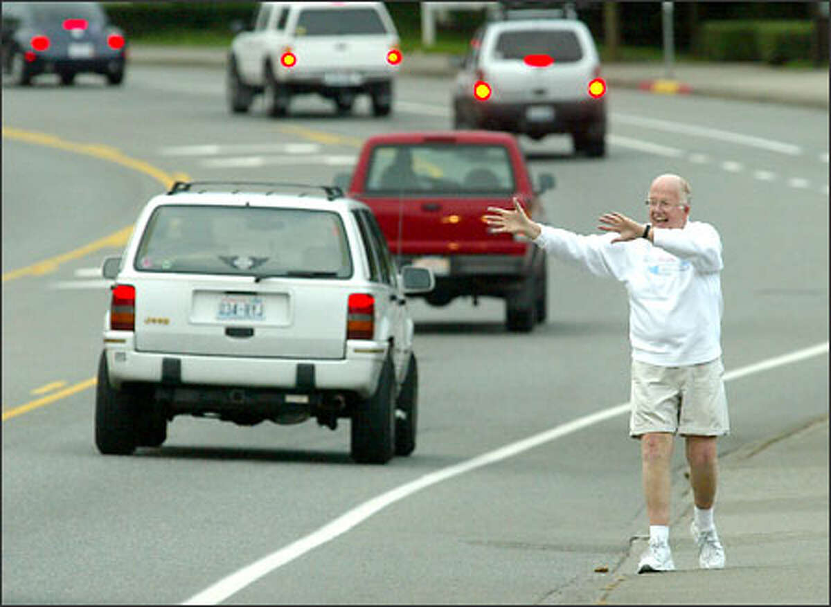 Bill Petter, 73, waves at passers-by during a recent early-morning walk along Lake Washington Boulevard in Kirkland, just as he has for 18 years.
