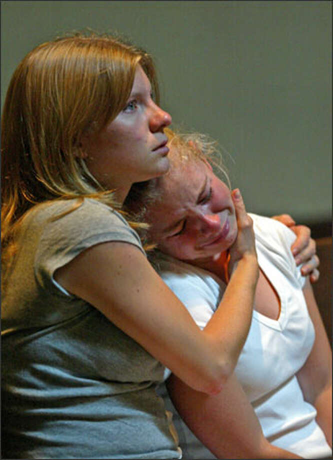 "During a mass at St. James Cathedral, 21-year-old Sarah Estill, left, comforts her 17-year-old sister, Jenny, both of Seattle. They were affected by the prayers for the victims of the July 7 bombings in London, which killed more than 50 people. Sarah, recently returned from England, said she was glad it wasn't bigger, while Jenny remarked, ""THis stupid war."" Photo: Karen Ducey, Seattle Post-Intelligencer / Seattle Post-Intelligencer"