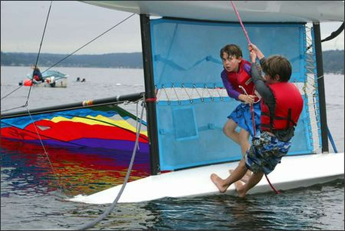 Harrison Grad, left, and Alec Wade, both 10, climb aboard their catamaran after they purposely capsized it Monday on the first day of cruising class through Sand Point Sail in Seattle.
