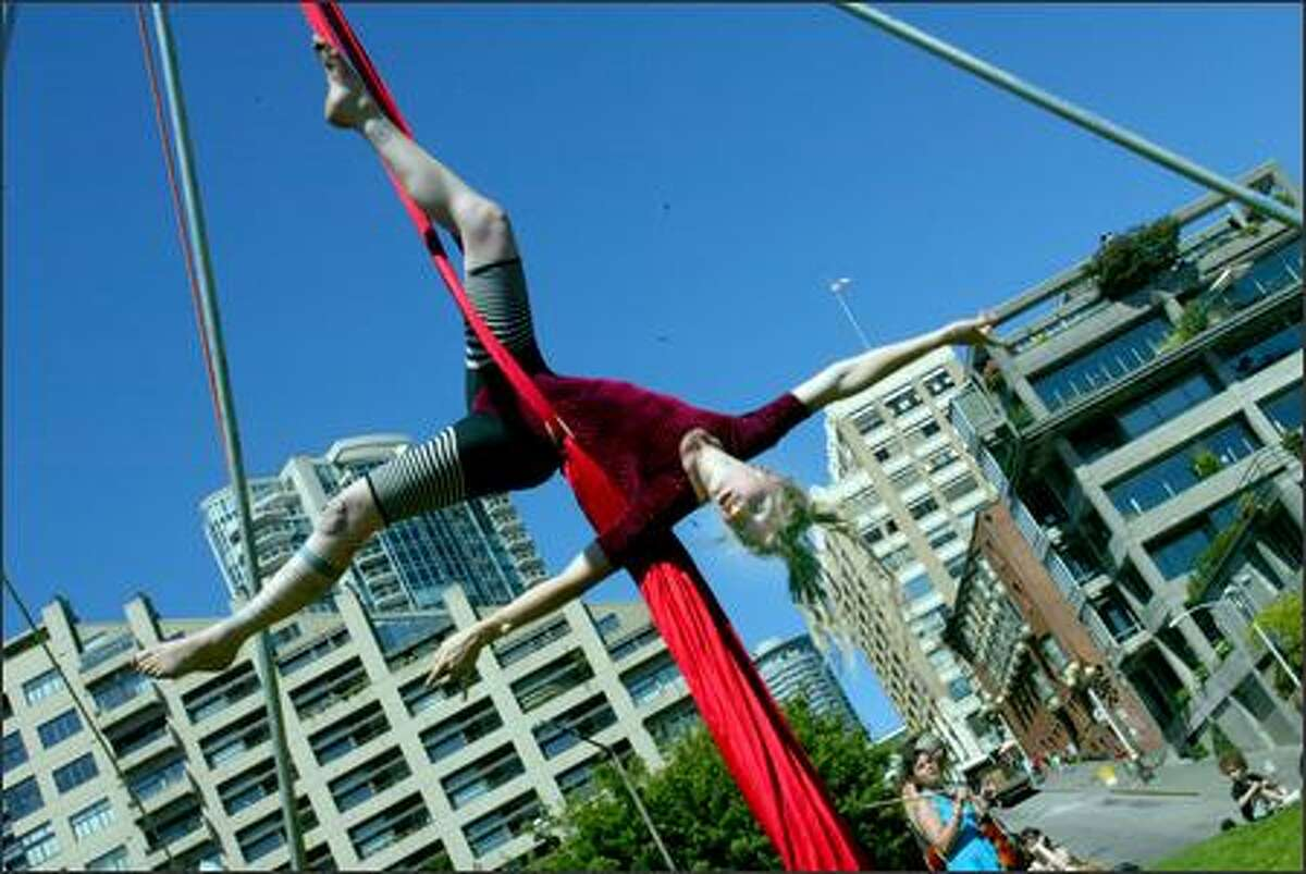 Autumn Augustus performs acrobatics on aerial silk with a group called Cirkus Pandemonium in Victor Steinbruek Park in Seattle on Tuesday. When asked if she was feeling the heat Augustus replied