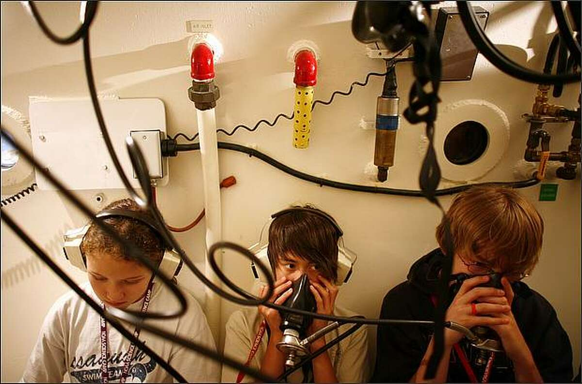 Students, from left, Lily Newton, 12, Noah Genatossio, 12, and Brock Breed, 13, learn about the hyperbaric chamber at National Oceanic and Atmospheric Administration's Sandpoint dive facility during a science camp.