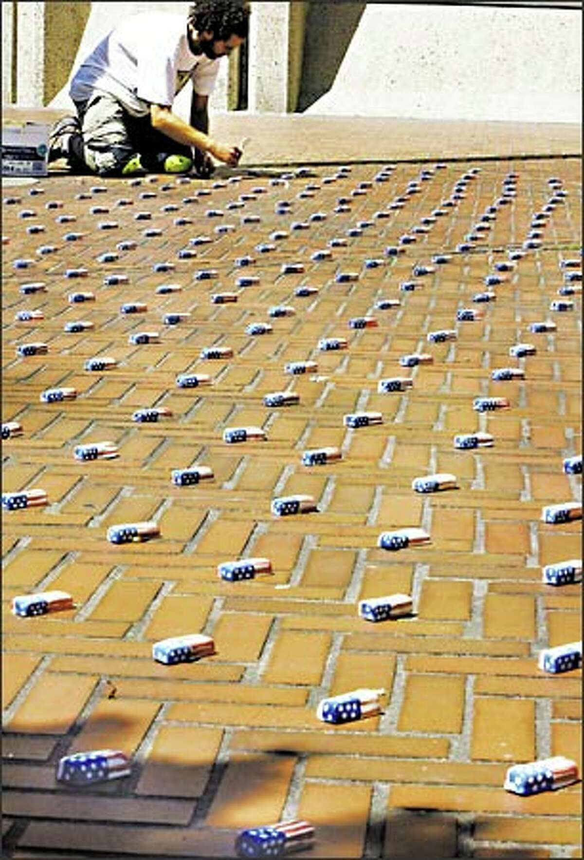Ceramic artist Randolph Sill lays out 887 tiny flag-draped caskets he made on the Second Avenue plaza of the Federal Building in downtown Seattle. He had a permit to display the exhibit for one day -- Monday. The caskets represent the American soldiers killed in the Iraq war.