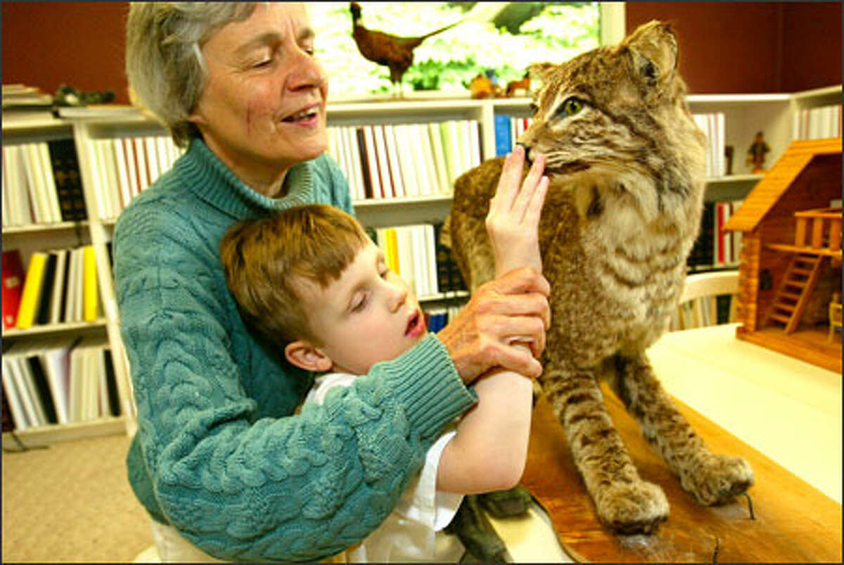 Carolyn Meyer, director of the Louis Braille School in Edmonds, introduces Tristan Freckleton, 5, to a stuffed bobcat. The school provides a summer camp for blind youngsters, teaching them life skills and how to deal with their impairments. The new K-8 school will welcome students for the first time in September.