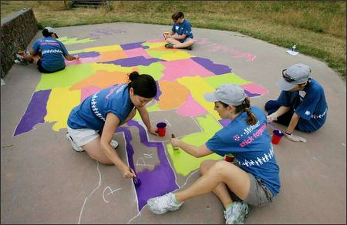 Susan Newman of Sammamish (left), Jennifer Spindel of Kirkland and other volunteers paint a county map of Washington outside Summit K-12 School in Seattle on Thursday. The women were among the more than 250 T-Mobile employee volunteers that gave the northeast Seattle School a makeover for its after school space as part of Huddle Up, the Seattle-based company's national community outreach program.