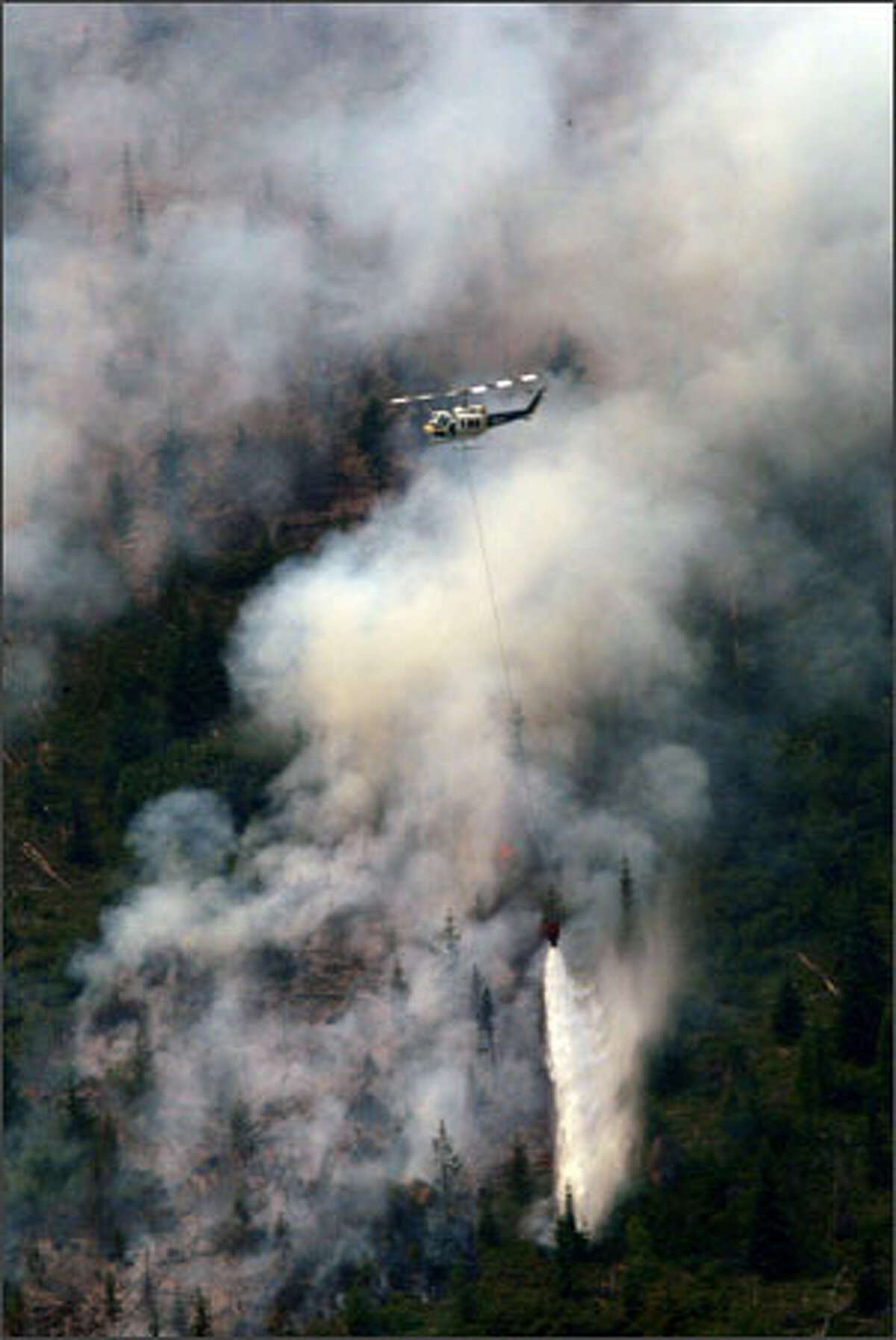 Helicopters drop water on a lightning-sparked wildfire near Leavenworth, in the Icicle Creek area.