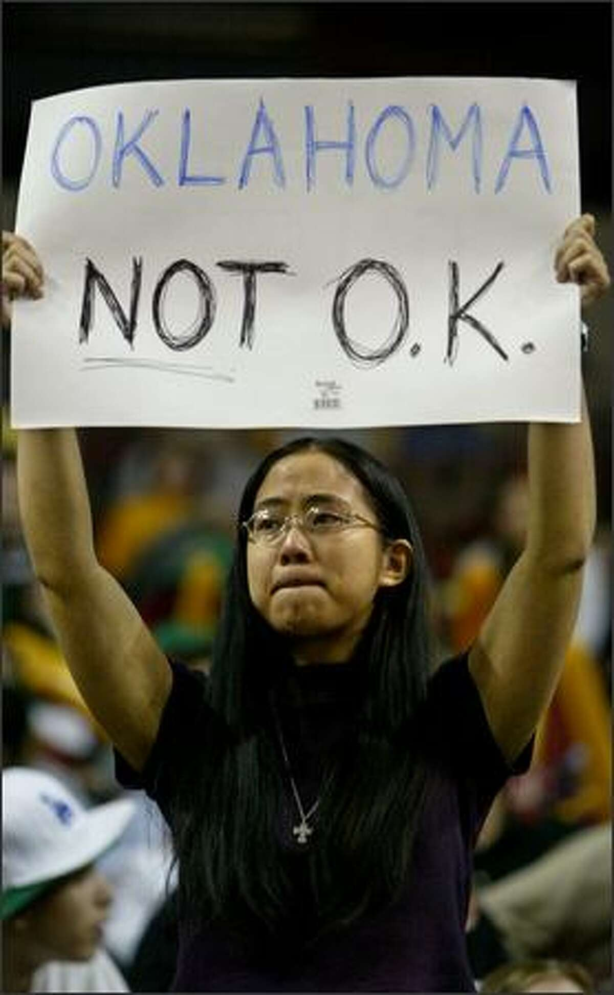 Seattle Storm season ticket holder Becky Chow holds up a sign protesting the sale of the team and the Seattle SuperSonics as other fans cheer during a game against the Sacramento Monarchs. The Monarchs won, 74-61.