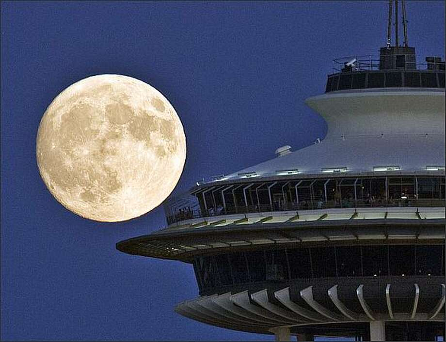 Visitors to the Space Needle enjoy a full moon. Photo: Grant M. Haller, Seattle Post-Intelligencer / Seattle Post-Intelligencer