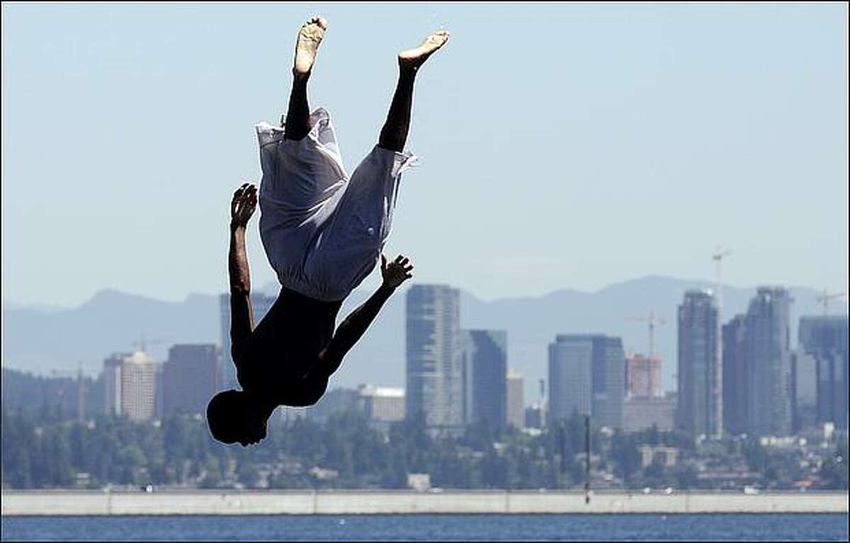 With downtown Bellevue behind him, Antonio Jones, 17, of Seattle flips while jumping off the diving board at Mount Baker Beach.