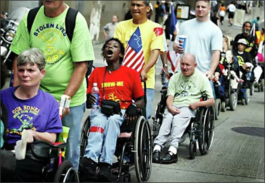 Nearly 250 disabled protesters, including Barbara Moore of Baltimore, Md., center in red, travel to the Federal Building on First Avenue Monday from the Westin Hotel, where the annual Governors' Association Conference in being held. The group went to the Federal Building to ask regional HUD Director John Meyers to send their complaints about the current housing voucher system to Washington D.C. Photo: Joshua Trujillo, Seattlepi.com / seattlepi.com