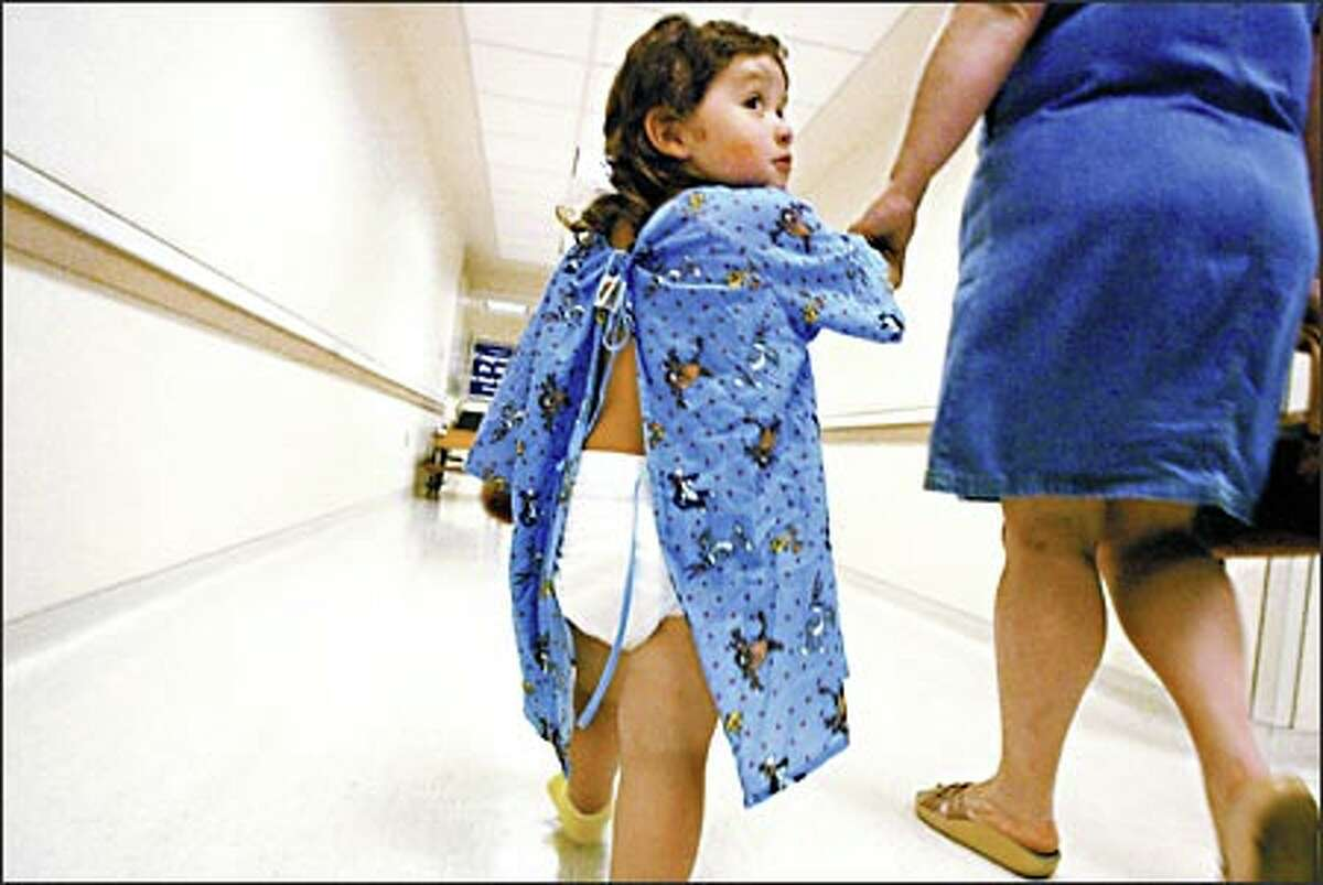 Angelito Haney, age 2, heads down the hallway at Children's Hospital for dental surgery accompanied by his mother, Tammy Haney. Pediatric dental surgery is one of the most common surgeries performed at Children's Hospital, with many families traveling from as far away as Wyoming for care.