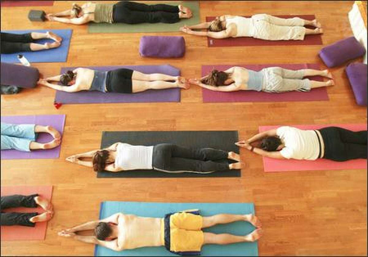 Students hold a pose on their mats during a yoga class at Samadhi Yoga Center on Capitol Hill.