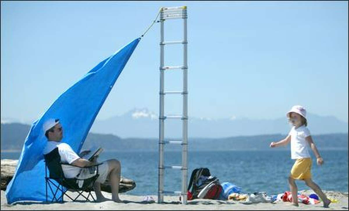 Made in the tarp-shade: Dave McPhee and his daughter Anna, 5, find a way to beat the heat Thursday on Seattle's Alki Beach.