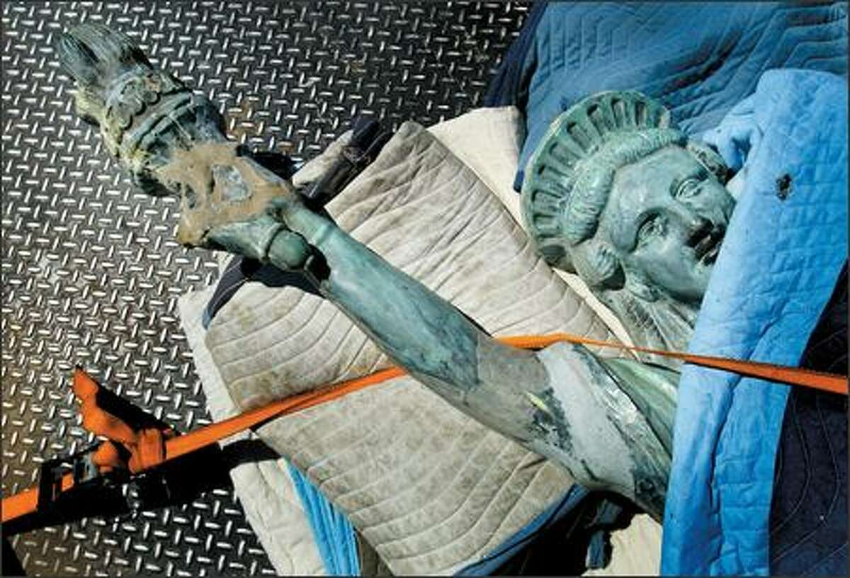 The miniature Statue of Liberty on Seattle's Alki Beach is tied down for transport after it was removed Thursday as part of a restoration project.