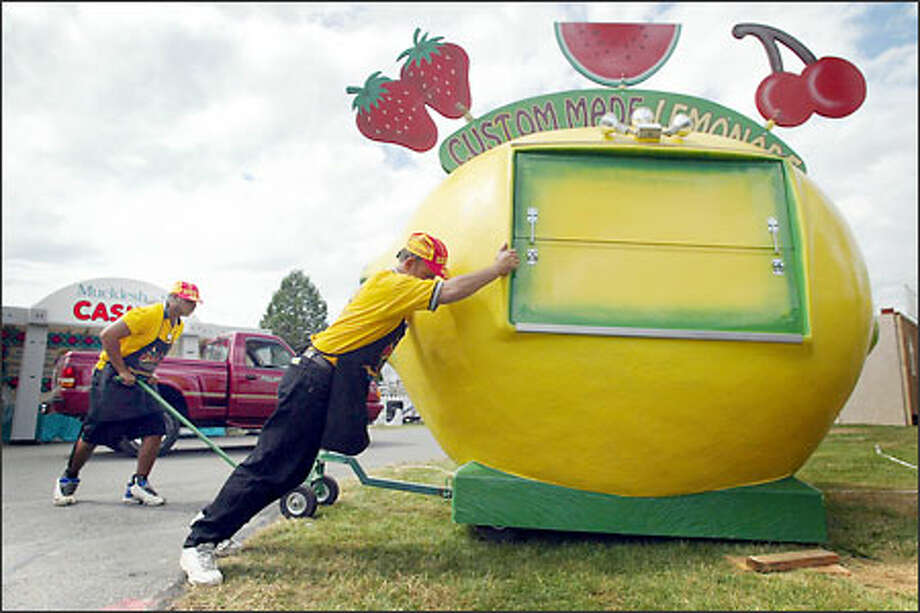 "Christopher Turpin, left, and Robert Kittle of Phoenix push their lemonade stand into place at the King County Fairgrounds in Enumclaw yesterday. The fair, which officially opens today, is returning to its ""old-time country"" roots, say organizers, with less glitz and more family-oriented entertainment. Photo: Joshua Trujillo, Seattlepi.com / seattlepi.com"